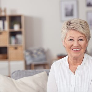 photodune-11969640-smiling-middle-aged-woman-sitting-at-the-sofa-l
